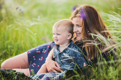Mother and son hugging on meadow. Mother and son hugging in the grass Stock Photos