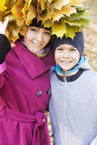 Mother and son hugging in the park. In autumn with leaves Stock Photo