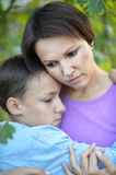 Mother and son hugging. Portrait if young mother and her preteen son hugging, looking serious Royalty Free Stock Photography