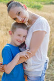 Mother and son hugging in wheat field. Mother and son hugging among wheat field Royalty Free Stock Image