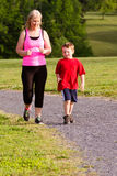Mother and son jogging for exercise. Outdoors stock photo