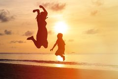 Mother and son jumping at sunset beach Royalty Free Stock Images