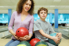 Mother and son keep balls and sit in bowling club Stock Image