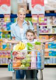 Mother and son  keeps cart full of products Stock Images