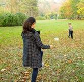 Mother and son kicking ball Stock Photos