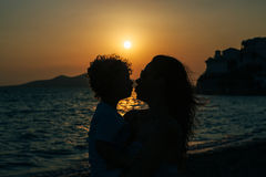 Mother and son kissing at sunset on beach stock photo