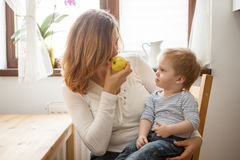 Mother and son at the kitchen eating an apple Royalty Free Stock Photography