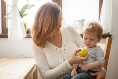 Mother and son at the kitchen eating an apple Stock Photography