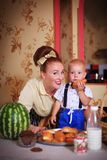 Mother and son in the kitchen with pastries. Studio shot, home interior royalty free stock images