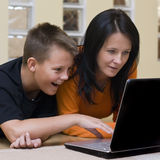 Mother and son with laptop. Mother and her teenage boy lying down on the floor of the living room, using a laptop computer together Royalty Free Stock Photography