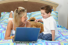 Mother and Son with Laptop in Bed Royalty Free Stock Photo
