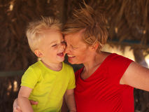 Mother and son. Laughing mother and son hugging each other in a small beach house Royalty Free Stock Photo