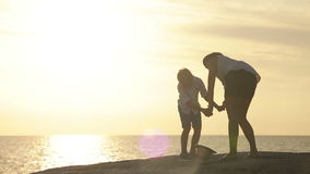 Mother and son laughing on the seashore with great sunset stock video footage