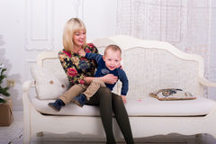 Mother and son laughing while. Sitting on the couch Stock Images