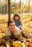 Mother and son  lay on autumn leaves Stock Images