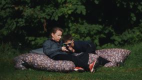 Mother and son laying down on a giant pillow in a park and uses smartphone. Mother and son laying down on a giant pillow under tree in a park and uses smartphone stock footage
