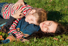 Mother and son laying on the green grass Royalty Free Stock Photo