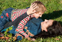 Mother and son laying on the green grass Stock Photos
