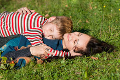 Mother and son laying on the green grass Royalty Free Stock Image