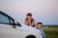 Mother and Son Leaning on Front of the White Car Royalty Free Stock Photos