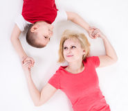 Mother and the son lie on a floor having joined hands. Stock Images