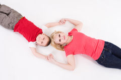 Mother and the son lie on a floor having joined hands. Stock Photos