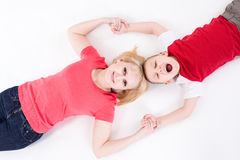 Mother and the son lie on a floor having joined hands. Royalty Free Stock Photo