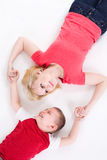 Mother and the son lie on a floor having joined hands. Stock Image
