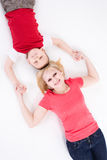 Mother and the son lie on a floor having joined hands. Stock Photography
