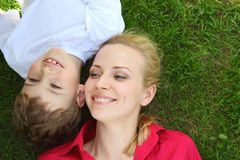 Mother and son lie  head to head on grass Stock Photo