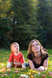 Mother and son lies on maple leaves. Mother and son lies on yellow maple leaves and smiles Royalty Free Stock Images
