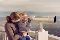 Mother and Son. Mother lifting her young son up to look throuhg a viewing binocular Stock Image