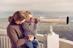 Mother and Son. Mother lifting her young son up to look throuhg a viewing binocular Royalty Free Stock Photography