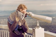 Mother and Son. Mother lifting her young son up to look throuhg a viewing binocular Stock Photo