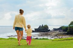 Mother, son look from cliff at Balinese temple Tanah lot. Happy child at walk with parent. Mother, baby son look from high cliff at beach, Balinese temple Tanah stock photography