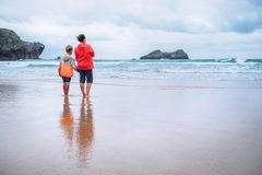 Mother and son look on waves on ocean coast line after the storm Stock Photo