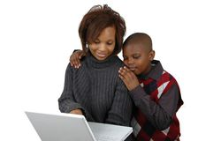 Mother and son looking at a co. Mputer against white background Royalty Free Stock Image