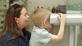 Mother and son looking through coin binoculars on the observation deck. Mother and son looking through coin binoculars or magnifier on the observation deck stock video footage