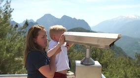 Mom and son looking through coin binoculars or magnifier on the observation deck. Mother and son looking through coin binoculars or magnifier on the observation stock video footage