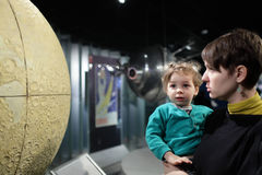 Mother with son looking at globe of moon Stock Image