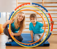Mother and son looking through hula hoops Royalty Free Stock Photo