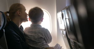 Mother and son looking out illuminator in plane stock video footage
