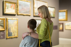 Mother and son looking at paintings in halls of museum. Positive italian mother and son looking at paintings in halls of museum Stock Images