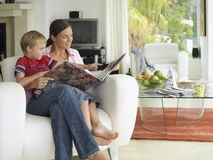 Mother and son (5-7) looking at photo album at home, boy in mother's lap in armchair, smiling Royalty Free Stock Photo