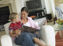 Mother and son (5-7) looking at photo album at home, boy in mother's lap in armchair, smiling (tilt) Stock Photo