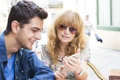 Mother and son looking at screen of mobile. Mother (woman) and son (teenage boy) with happy expression looking at the screen of a mobile phone Royalty Free Stock Photography
