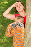 Mother and Son Looking At Something. A boy and his mother are looking at something interesting from behind a tree Royalty Free Stock Photos