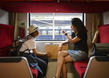 Mother and son looking through a train window as they enjoy a days travel at Thailand.  stock photos