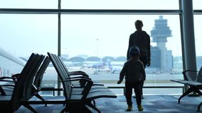 Mother with son of loving family waiting for flight at the airport. Slow motion. 60fps. 1920x1080. Mother with son of loving family waiting for flight at the stock video