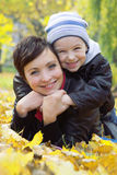 Mother and son lying on autumn leaves Stock Photos